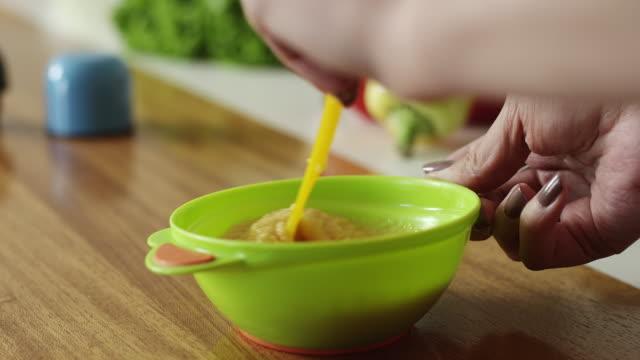 vídeos de stock, filmes e b-roll de mãe preparar comida para seu bebê - comida de bebê