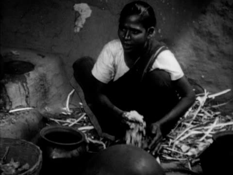 mother preparing meal ms soaking turning rice in bowl with hands eldest son ezdoss watching mother stirring cooking pot over fire inside one room hut... - dalit stock videos and b-roll footage