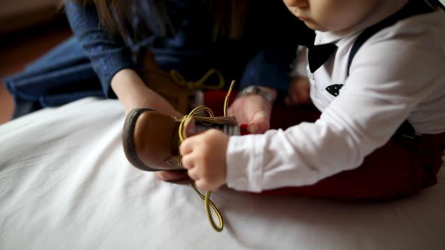 vídeos de stock, filmes e b-roll de matriz que prepara o filho para seu primeiro aniversário. mulher nova que amarra o cadarço da criança - amarrar