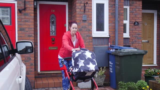 vídeos y material grabado en eventos de stock de preparación de la madre para correr con su bebé al aire libre - cochecito de bebé