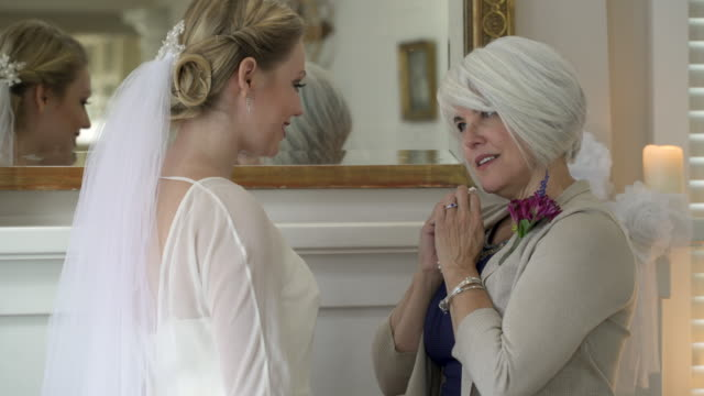 mother presenting daughter pearl necklace on wedding day. - daughter video stock e b–roll