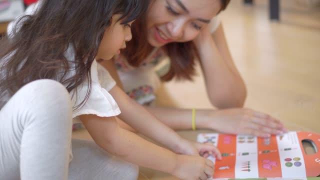 vídeos de stock e filmes b-roll de mother proudly watches her daughter learn the exercises. - soletrar