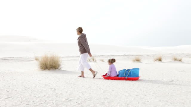 ws pan mother pulling daughter (2-3) on sled in white sands / white sands, new mexico, usa - ziehen stock-videos und b-roll-filmmaterial