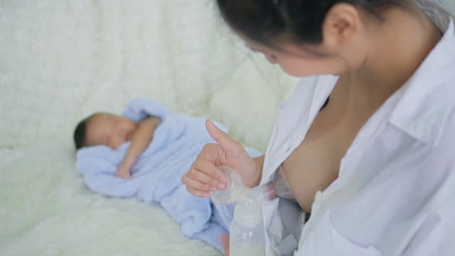 mother pumping milk from her breast for her newborn baby - baby milk stock videos & royalty-free footage