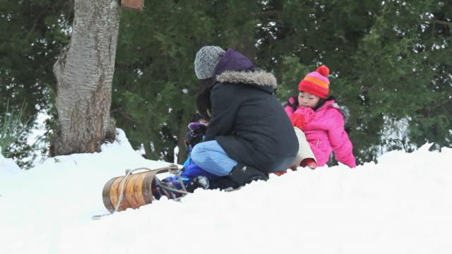 stockvideo's en b-roll-footage met ws ts tu mother pushing children (2-11) on sledge downhill in snow / richmond, virginia, usa - familie met drie kinderen