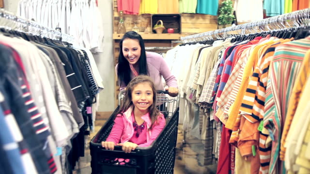 mother pushing girl in shopping cart - clothes shop stock videos & royalty-free footage