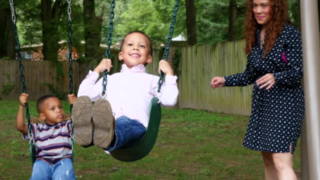 MS Mother pushing young son and cousin on swing set in backyard of home
