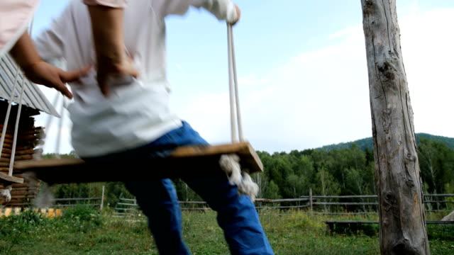 stockvideo's en b-roll-footage met moeder duwen jonge zoon op schommel in achtertuin - schommelen bungelen