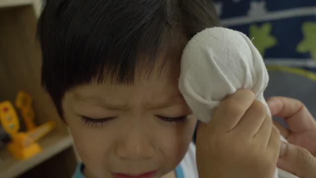 母親は男の子の頭に冷たい氷を置くが腫れている - 怪我点の映像素材/bロール