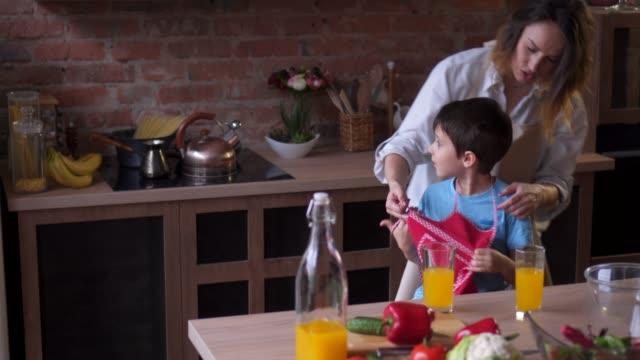 vídeos y material grabado en eventos de stock de madre pone el delantal a su pequeño hijo - delantal