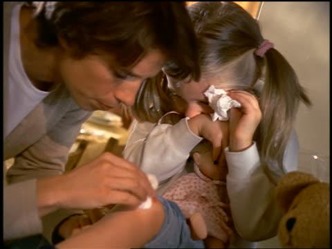 mother putting adhesive bandage on knee of small crying blonde girl / girl starts smiling - 絆創膏点の映像素材/bロール