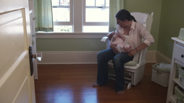 stockvideo's en b-roll-footage met ms pan mother putting baby daughter (3-5 months) down in crib / seattle, washington state, usa - schommelen schommelstoel