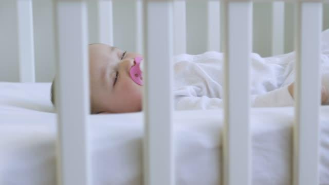 stockvideo's en b-roll-footage met mother putting baby daughter to sleep. - wieg