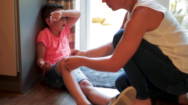 mother putting band aid on childs knee - assistance stock videos & royalty-free footage