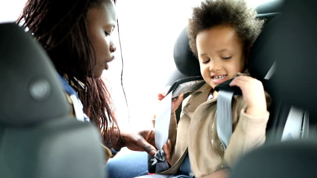 mother putting daughter into car seat - seat belt stock videos & royalty-free footage