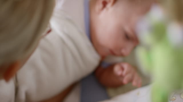 mother putting her baby boy to bed - pendere video stock e b–roll