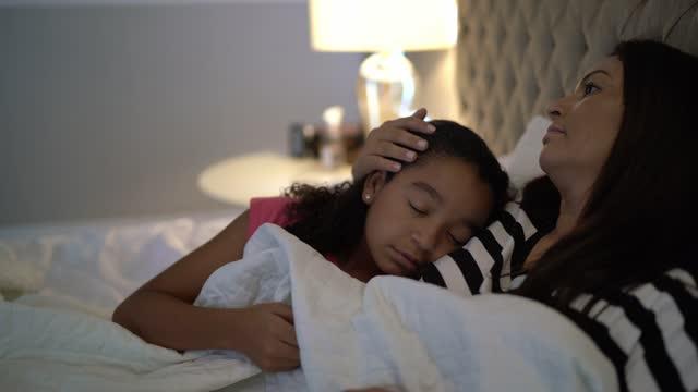 stockvideo's en b-roll-footage met moeder die haar dochter voor een dutje zet - dochter