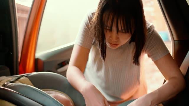 vidéos et rushes de mère mettant le petit garçon dans le siège d'auto de chéri - habitacle de voiture
