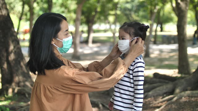 mother putting on a medical mask on her daughter in - prevention stock videos & royalty-free footage