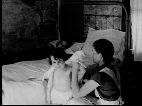 1935 B/W MS mother putting pajamas on young girl and lifting her into bed beside her older sister / run down walls / USA