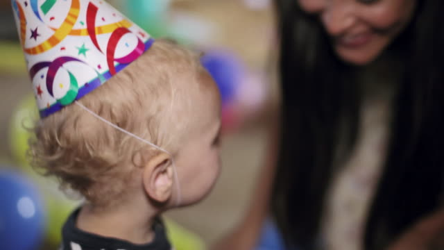 cu mother putting party hat on cute toddler head / santa monica, ca, united states    - party hat stock videos & royalty-free footage