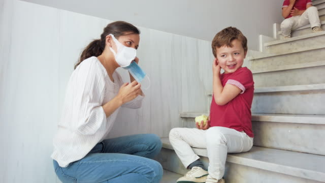 mother putting protective face mask on her child before going outdoors - surgical mask stock videos & royalty-free footage
