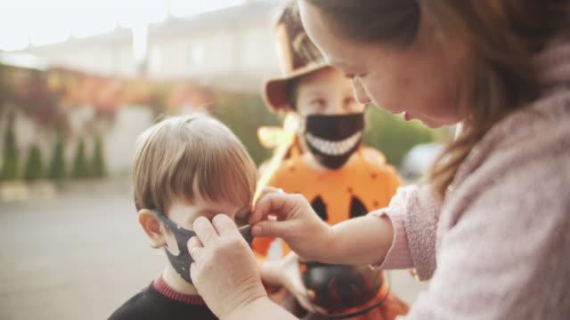 mutter setzt schützende gesichtsmaske auf ihr kind während covid-19 pandemie an halloween - halloween stock-videos und b-roll-filmmaterial