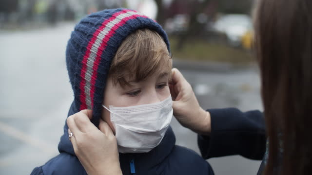 mother putting protective face mask on her child - air pollution stock videos & royalty-free footage
