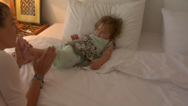 ms, zi, mother putting shoes on  daughter (12-17 months) lying on bed - 12 17 months stock videos & royalty-free footage