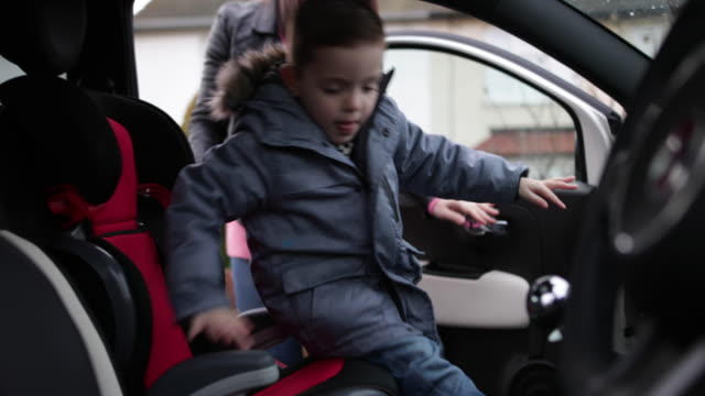 mother putting son in car seat safely - vinter bildbanksvideor och videomaterial från bakom kulisserna