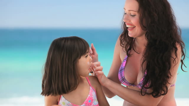 cu mother putting sunscreen on daughter sitting on beach / cape town, western cape, south africa - sun cream stock videos and b-roll footage