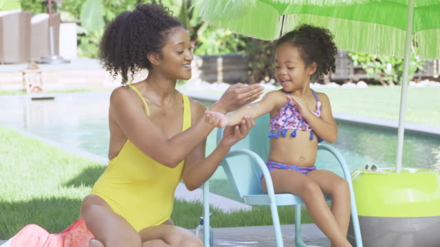 mother putting sunscreen on daughter - sonnencreme stock-videos und b-roll-filmmaterial