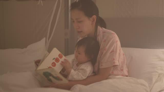 la madre lesse un libro di storie al bambino. - letteratura video stock e b–roll