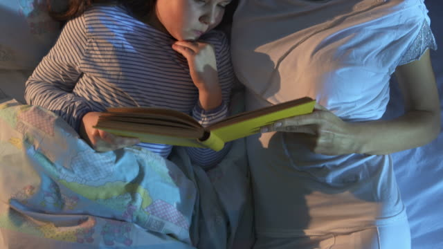 hd crane: mother reading a bed time story - storytelling stock videos and b-roll footage