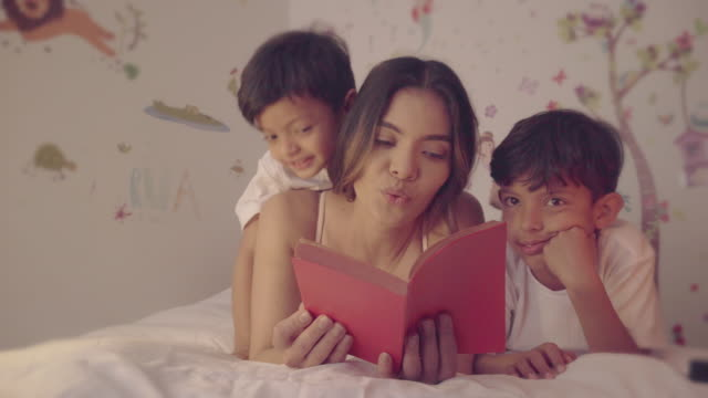 a mother reading a story for his children - bedtime stock videos & royalty-free footage