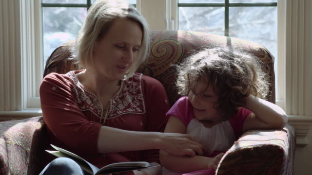 mother reading a storybook to her young daughter - sitting stock videos & royalty-free footage