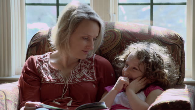 mother reading a storybook to her young daughter - reading book stock videos & royalty-free footage