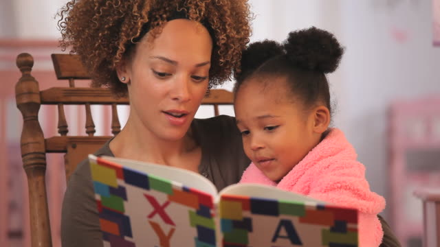 MS Mother reading alphabet book to daughter (4-5) in nursery / Richmond, Virginia, USA