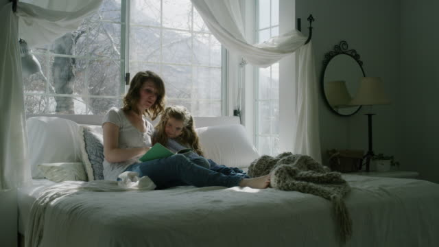 mother reading book on bed to daughter near bay window / pleasant grove, utah, united states - erkerfenster stock-videos und b-roll-filmmaterial