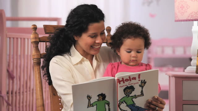 MS Mother reading book to baby girl (19-23 months) in nursery / Richmond, Virginia, USA