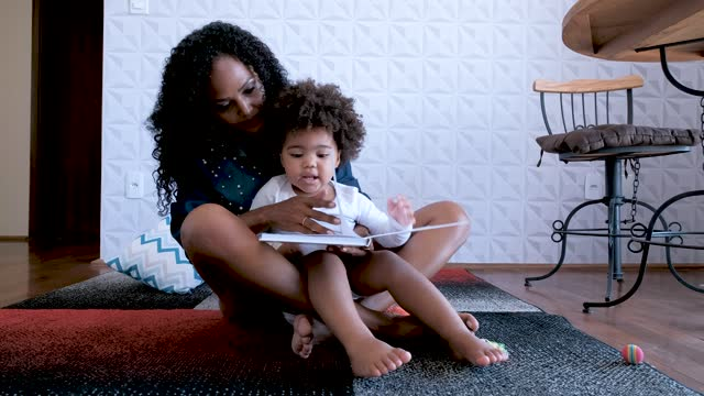 mother reading book to daughter. sitting on the carpet in the living room. - 35 39 years stock videos & royalty-free footage