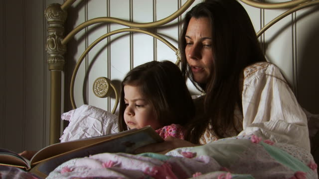 mother reading daughter bedtime story in bed - picture book stock videos and b-roll footage