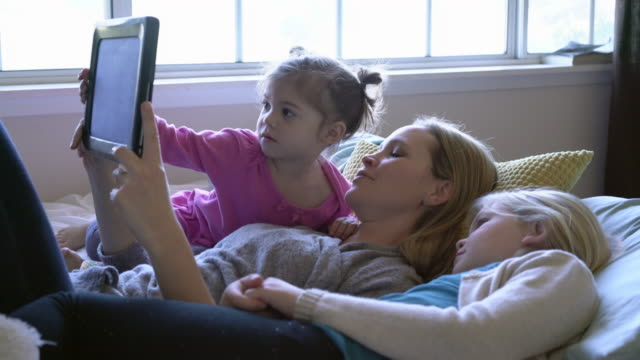 ws mother reading to her daughters in bed from a digital tablet - familie mit zwei kindern stock-videos und b-roll-filmmaterial