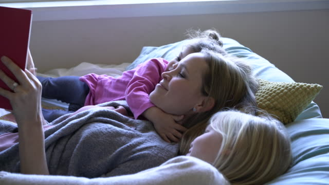 ms mother reading to her daughters in bed - auf dem rücken liegen stock-videos und b-roll-filmmaterial