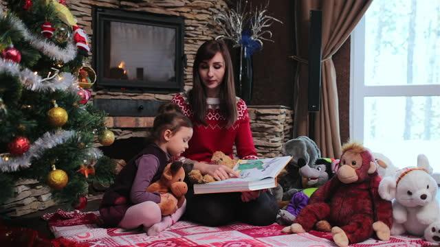 vídeos y material grabado en eventos de stock de madre le lee un cuento de hadas para niños a su hija cerca del árbol de navidad. - narrar