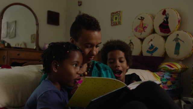 mother reads book to son and daughter in their bedroom at home - family with two children stock videos & royalty-free footage