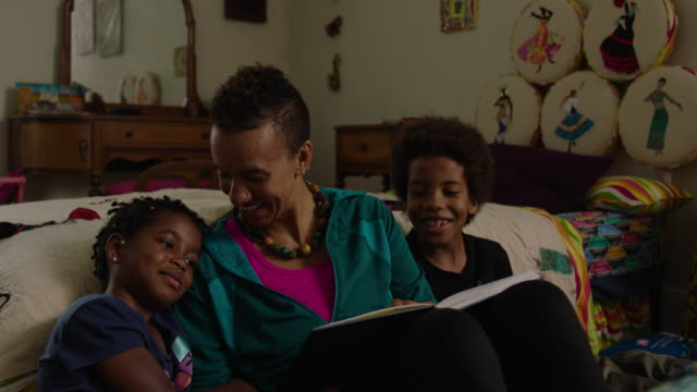 mother reads book to son and daughter in their bedroom at home - storytelling stock videos & royalty-free footage