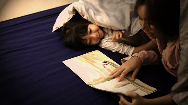 mother reads stories to her daughter under blanket regularly before bedtime. - bedtime stock videos & royalty-free footage