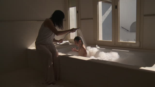 mother rinse little girl hair in bath - bubble bath stock videos and b-roll footage