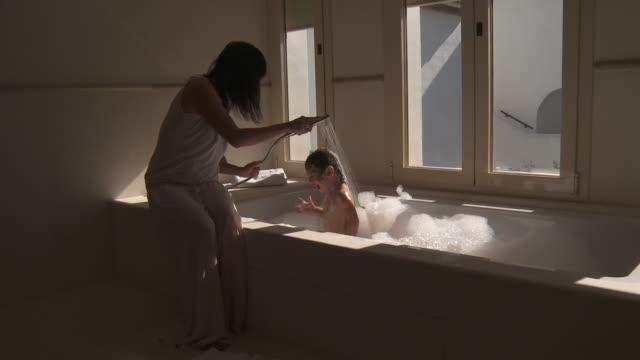 mother rinse little girl hair in bath - 浴室点の映像素材/bロール